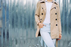 Slim girl in jeans, a beige coat and white shirt outdoors in spring. Copy space Royalty Free Stock Images