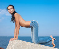 Slim girl in jeans outdoors. Attractive young woman at the sea Royalty Free Stock Photography