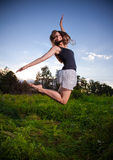 Slim girl jumping high on field Stock Photo