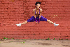 Slim girl jumps on background of wall Royalty Free Stock Photography