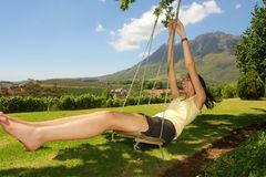 Slim girl laughes on swing Stock Image