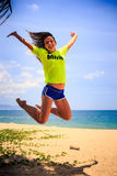 Slim girl in lemon t-shirt jumps with legs backward over sand Royalty Free Stock Images