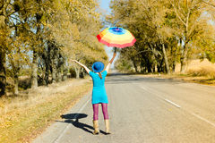 Slim girl in lilac pants walking under parasol Stock Image