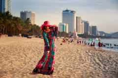 slim girl in long and big hat on beach against city sea Royalty Free Stock Image