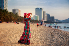 slim girl in long and big hat on beach against city sea Stock Photo