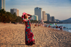 slim girl in long and big hat looks at sun on beach in city Stock Image