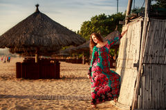 Slim girl in long and big red hat leans on reed wall on beach. Slim brunette longhaired girl in long colorful dress and big red hat leans on reed wall on beach Stock Image