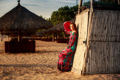 Slim girl in long and big red hat leans on reed wall on beach. Slim brunette longhaired girl in long colorful dress and big red hat leans on reed wall on beach Royalty Free Stock Image