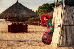 Slim girl in long and big red hat leans on reed wall on beach. Slim brunette longhaired girl in long colorful dress and big red hat leans on reed wall on beach Royalty Free Stock Photos