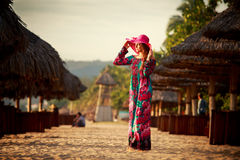 Slim girl in long and big red hat stands among beach umbrellas Stock Photo