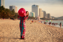 Slim girl in long holds big hat on beach against city sea Royalty Free Stock Images