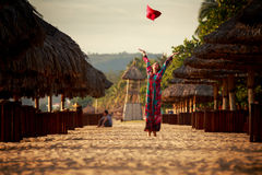 slim girl in long throws up big red hat among reed umbrellas Stock Image