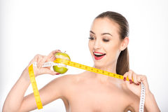 Slim girl measuring fruit by tape Stock Photography