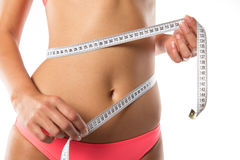 A slim girl measuring her waist. Royalty Free Stock Images