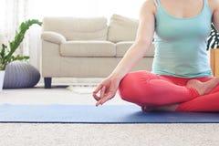 Slim girl meditating in lotus pose on yoga mat in living room Royalty Free Stock Photos