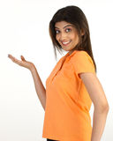 Slim girl in pointing action. With orange dress Royalty Free Stock Photos