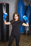 Slim girl posing in boxing gloves. She fulfills blows in the gym Stock Photo