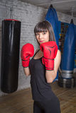 Slim girl posing in boxing gloves. She fulfills blows in the gym Stock Image
