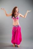 Slim Girl in Purple Orient Dance Costume Poses. Beautiful slim brunette girl in purple orient dance costume shows dance position hands sideward posing in studio Royalty Free Stock Image