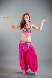 Slim Girl in Purple Orient Dance Costume Poses. Beautiful slim brunette girl in purple orient dance costume shows dance position hands sideward posing in studio Royalty Free Stock Photos