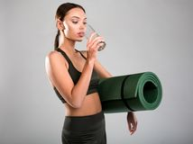 Slim girl quenching thirst after fitness classes. Nice looking woman in slinky sports costume drinking water. She is holding yoga mat under armpit. Isolated on Royalty Free Stock Photography