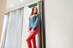 Slim girl with redheads chooses clothes. woman in red leather pants posing in fitting room bottom view stock images