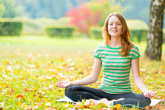 Slim girl relaxing sitting in the lotus position Stock Images