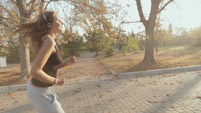 Slim girl runing through the park and listening to stock video