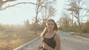 Slim girl running through the park in morning stock video