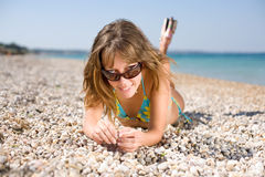 Slim girl on seashore. Pretty young woman lying down on sand looking at camera on top of tinted sunglasses Royalty Free Stock Photography
