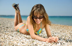 Slim girl on seashore. Girl lying down on sand looking at camera on top of tinted sunglasses Stock Image
