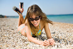 Slim girl on seashore. Pretty young woman lying down on sand looking at camera on top of tinted sunglasses Stock Images