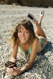 Slim girl on seashore. Slim young woman with tinted sunglasses in her hands lying down on heat pebble looking at camera laughing. Vertical composition Royalty Free Stock Images