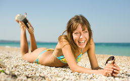 Slim girl on seashore. Slim young woman with tinted sunglasses in her hands lying down on heat pebble looking at camera laughing. Horizontal composition Stock Photography