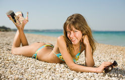 Slim girl on seashore. Slim girl with tinted sunglasses in her hands lying down on heat pebble looking at camera smiling Stock Photos
