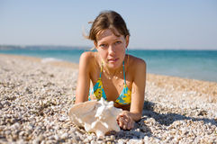 Slim girl with shell on seashore Stock Photo