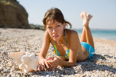Slim girl with shell on seashore Stock Photography