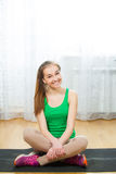 Slim girl sitting relaxed on yoga mat after work out Royalty Free Stock Photos