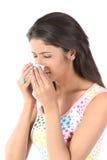 Slim girl sneezing with tissue paper stock photo