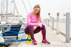 Slim girl in sports wear resting after exercise in seaport, healthy active lifestyle Royalty Free Stock Image