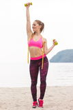 Slim girl in sportswear with centimeter exercising with dumbbells on beach, sports lifestyle, slimming concept Stock Photos