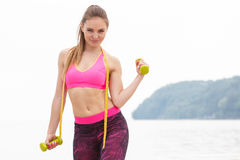 Slim girl in sportswear with centimeter exercising with dumbbells on beach, sports lifestyle, slimming concept Royalty Free Stock Images
