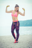 Slim girl in sportswear with centimeter exercising with dumbbells on beach, sports lifestyle, slimming concept Royalty Free Stock Photography