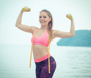 Slim girl in sportswear with centimeter exercising with dumbbells on beach, sports lifestyle, slimming concept Royalty Free Stock Photo