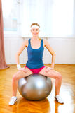 Slim girl in sportswear sitting on fitness ball Royalty Free Stock Image