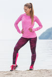 Slim girl in sporty clothes exercising on beach at sea, healthy active lifestyle Royalty Free Stock Photography
