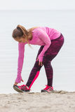 Slim girl in sporty clothes exercising on beach at sea, healthy active lifestyle Stock Photography