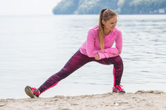 Slim girl in sporty clothes exercising on beach at sea, healthy active lifestyle Royalty Free Stock Photos