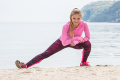 Slim girl in sporty clothes exercising on beach at sea, healthy active lifestyle. Slim girl wearing sporty clothes and exercising or stretching on beach at sea Stock Images