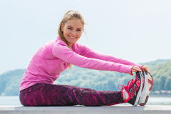 Slim girl in sporty clothes exercising by the sea, healthy active lifestyle Stock Photos